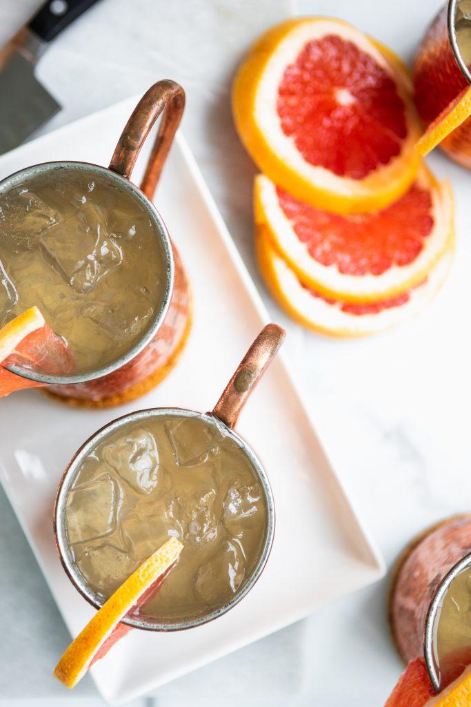 Grapefruit moscow mules overhead - copper mug with deep eddy grapefruit vodka and fresh grapefruit slices.