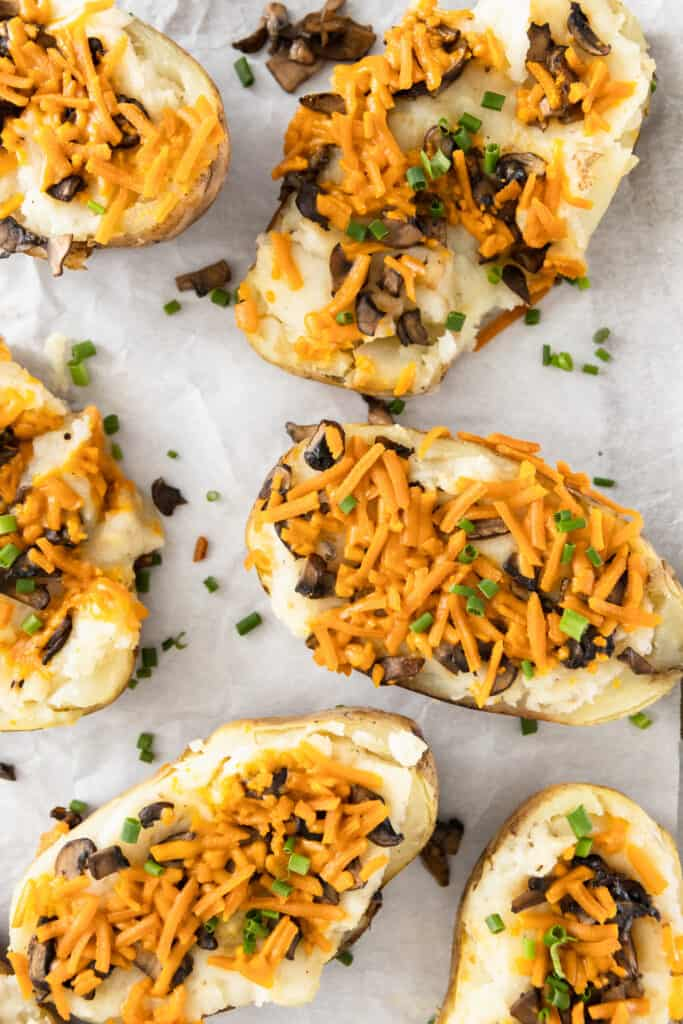 Twice baked potatoes with mushrooms and vegan cheese shreds.