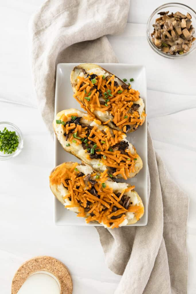3 twice baked potatoes on a plate with cheese, mushrooms and chives