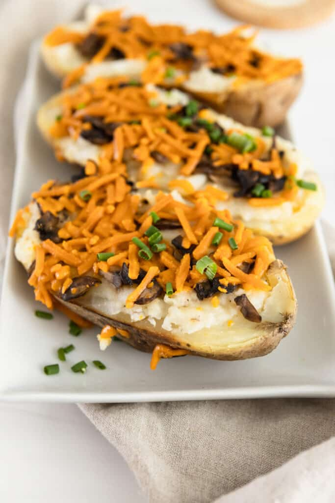 Close up of a twice baked potato with cheese shreds, mushrooms and chive sprinkles.