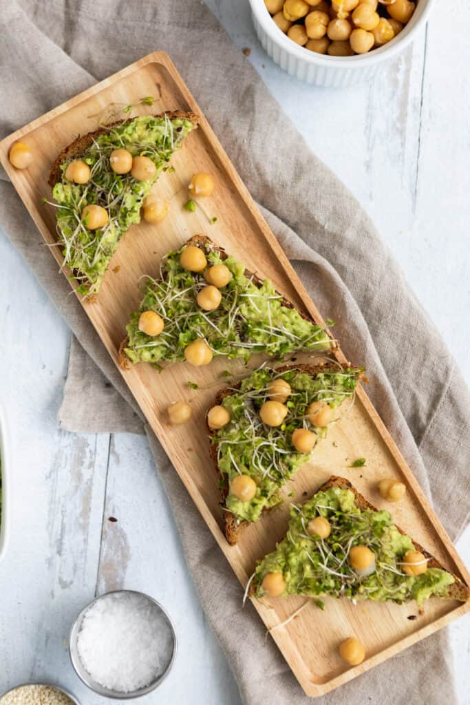Plant-based avocado toast slices with chickpeas and sprouts