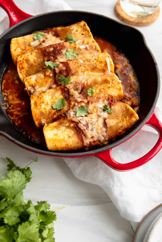 Enchiladas in a red casserole dish