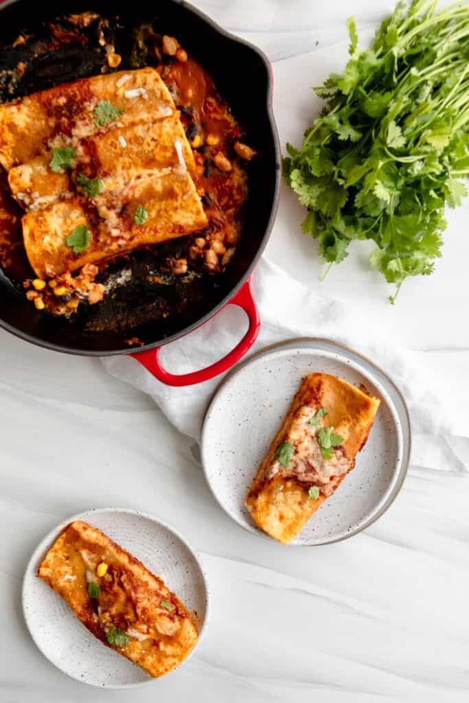 Enchiladas on plates garnished with cilantro and cast iron skillet
