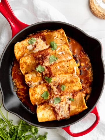 Black Bean Enchiladas overhead in a red cast iron skillet with cilantro garnish