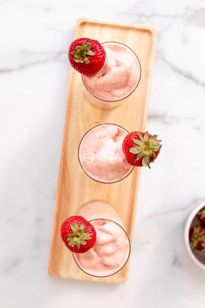 3 vegan strawberry mango smoothies with strawberry garnish on a tray