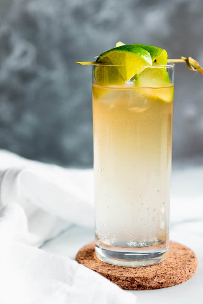 dark and stormy-ish cocktail in a highball glass with lime wedges