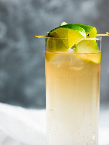 dark and stormy in a collins glass with lime garnish