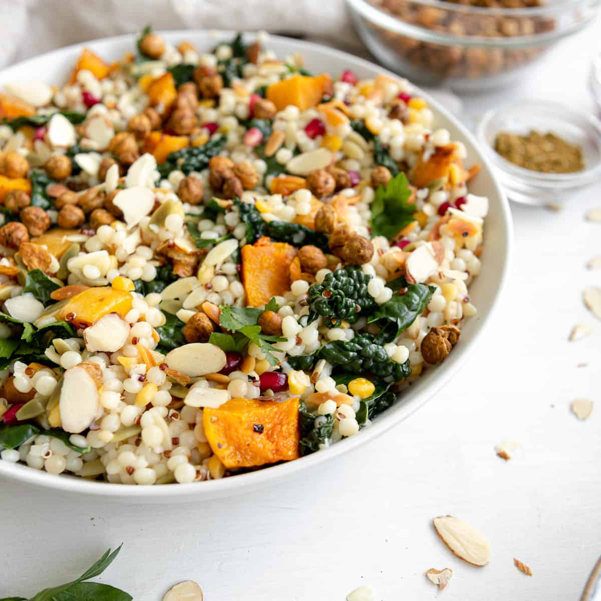 fall pearl couscous salad with butternut squash in a bowl with slivered almonds and pomegranate seeds